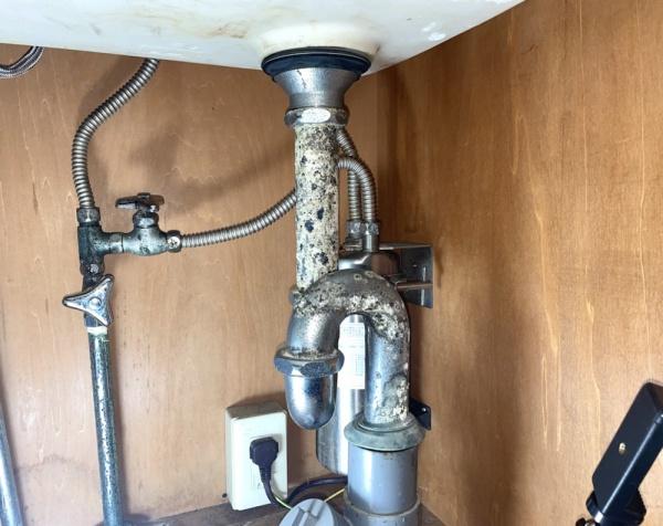 シンク下収納部。既設蛇口(海外製)、排水金具交換前。